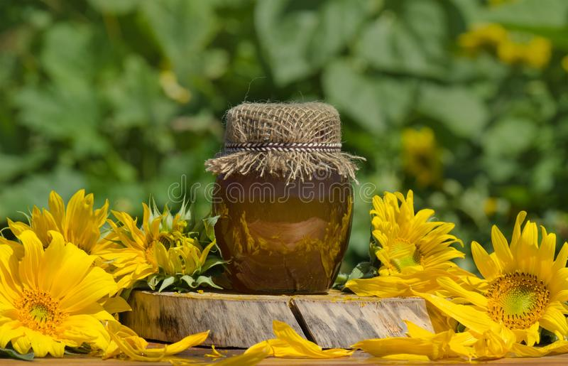 Jar of honey on wooden table. Jar of honey and sunflowers on old retro vintage wooden texture background. Jar of fresh honey  in field of wildflowers royalty free stock images