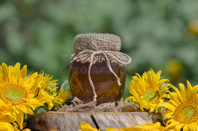 Jar of honey on wooden table. Jar of honey and sunflowers on wooden table over bokeh garden background. Jar of fresh honey  in field of wildflowers stock photography