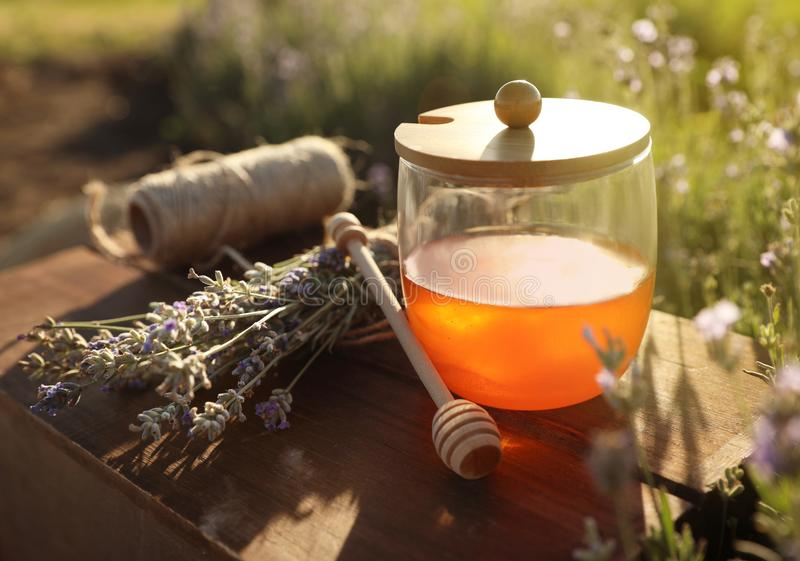 Jar of honey on wooden table. In lavender field stock images