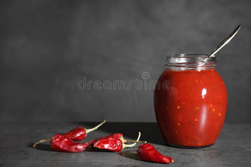 Jar of hot chili sauce with spoon and peppers on table. Space for text royalty free stock photos