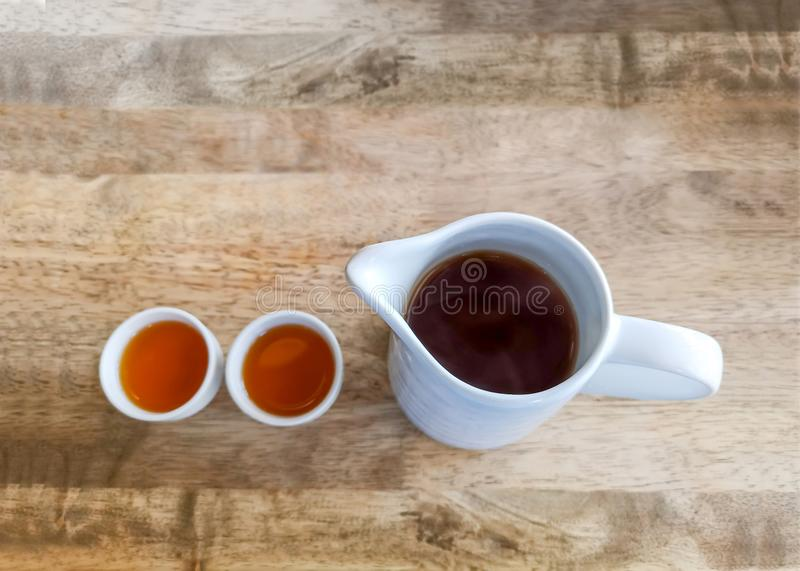 A jar of hot tea and two cups on brown wooden table for drinking time, top view image. A jar of hot tea and two cups on brown wooden table for drinking time stock photos