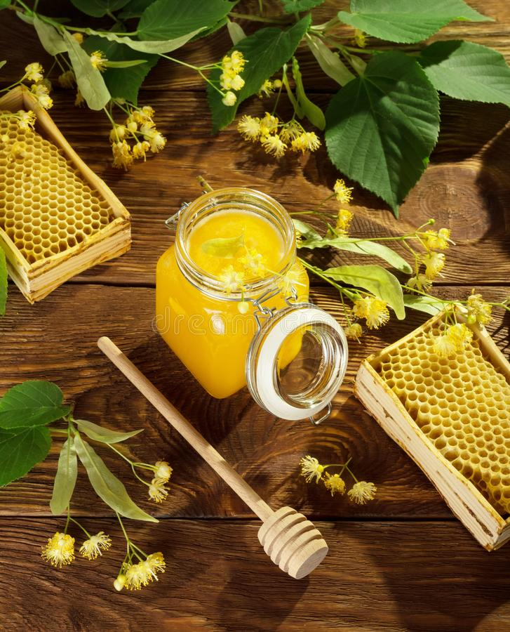 Jar of lime honey, frames with bee cells, spindle and Linden flowers on table. Jar of lime honey, frames with bee cells, spindle and Linden flowers, on wooden royalty free stock photo
