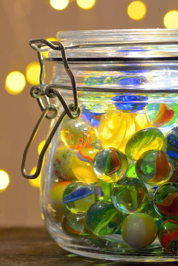 Jar of Marbles and Christmas lights stock photos