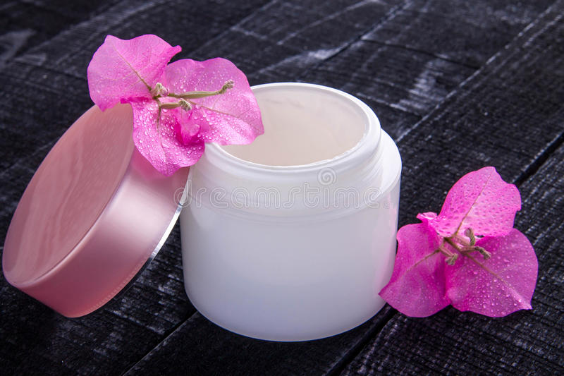 Jar of natural cream with pink flowers stock images