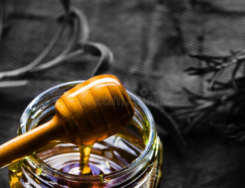 Jar of organic honey and wooden dripper. And textured background in mono royalty free stock photography