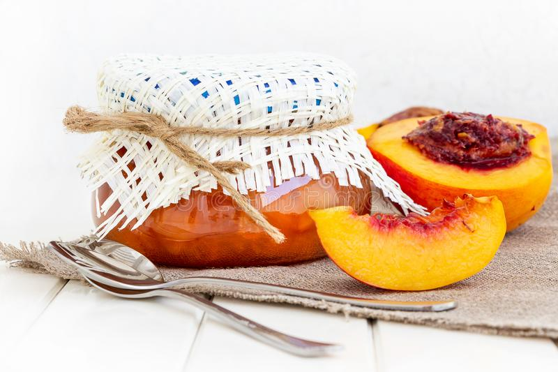 Jar with peach or nectarine jam. Half nectarine fruits. Burlap napkin. White wooden background. Selective focus. Copy space. Jar with peach or nectarine jam royalty free stock images