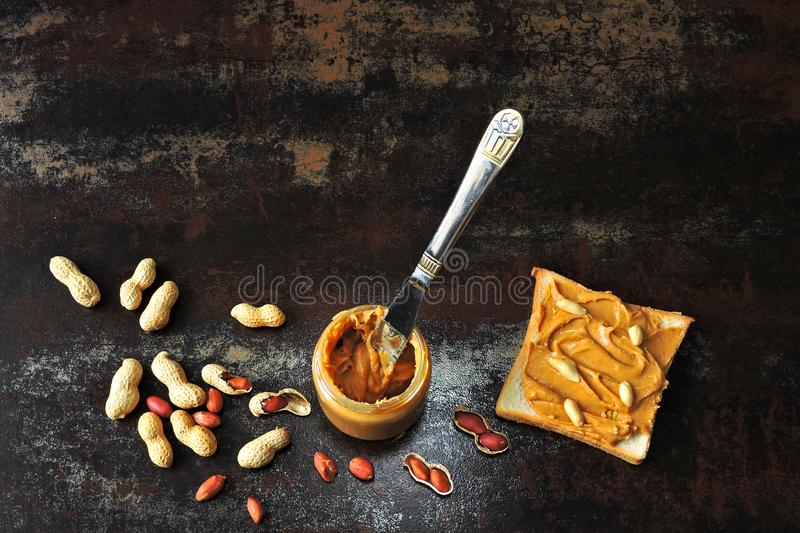 Jar of peanut butter, peanuts in a peel, apple slices and a knife. royalty free stock photo