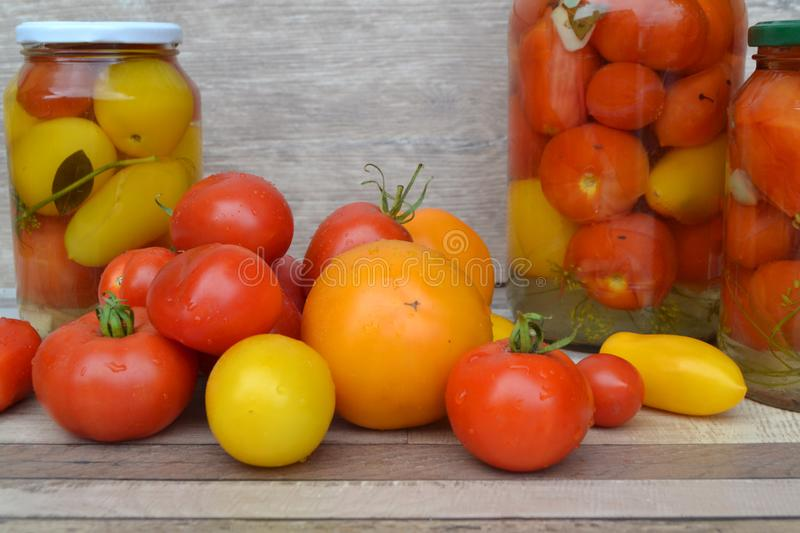 Jar of pickled small red and yellow cherry tomatoes. Fresh tomatoes. Healthy vegetable stock photography