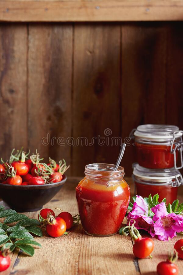 A jar of rose hip jelly and fresh rose hips royalty free stock photography