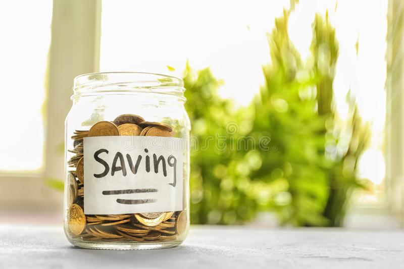 Jar for savings full of coins on table against blurred background stock image