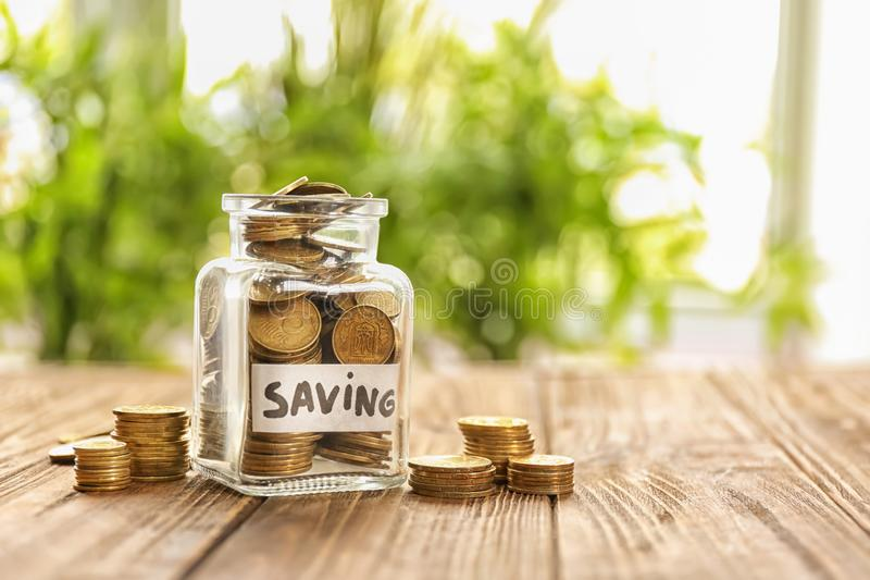 Jar for savings full of coins on wooden table against blurred background stock photo