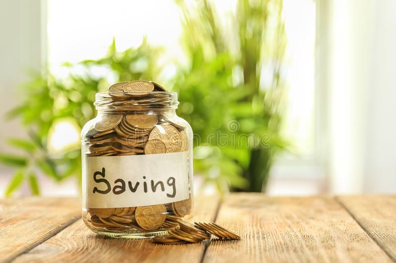 Jar for savings full of coins on wooden table against blurred background stock image
