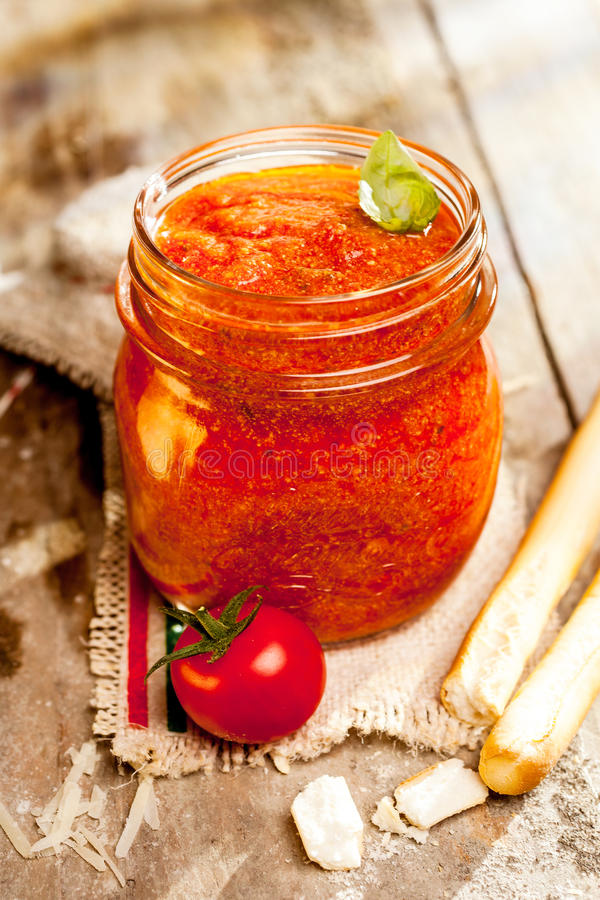 Jar of savory relish with grissini. Jar of savory relish or dip with Italian grissini or breadsticks on a cloth with the Italian national colors and fresh tomato royalty free stock photography