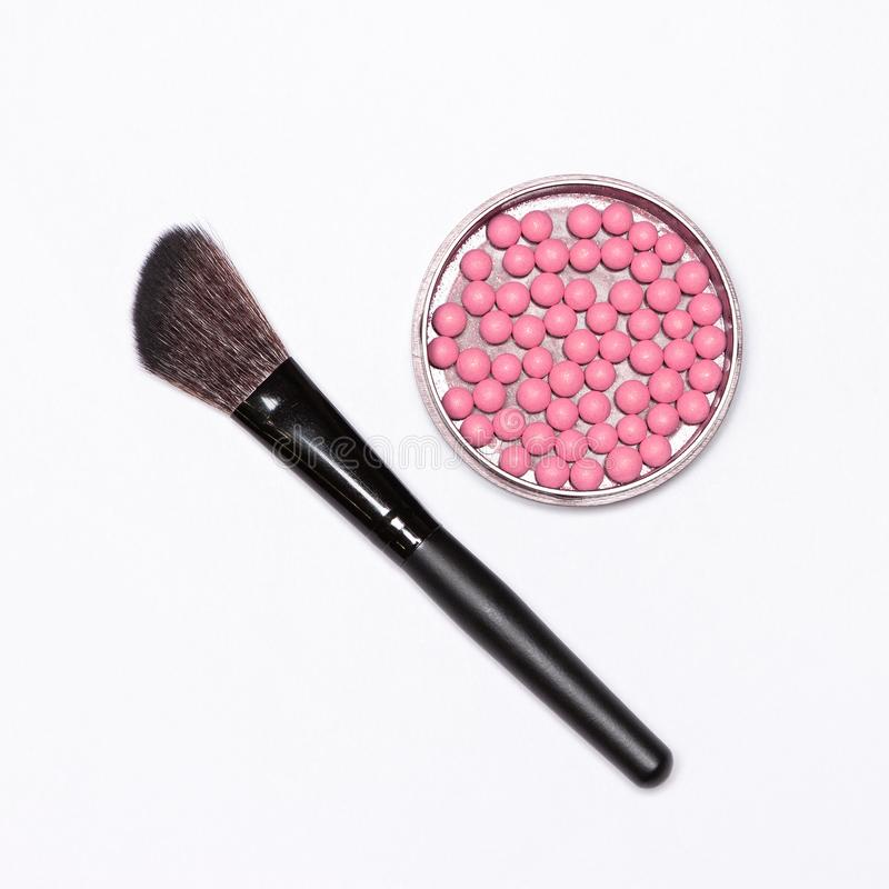 Jar of shimmer blush balls pink color with make-up brush. On white background stock photos
