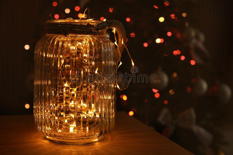 Jar with lights and blurred Christmas tree on background stock photo