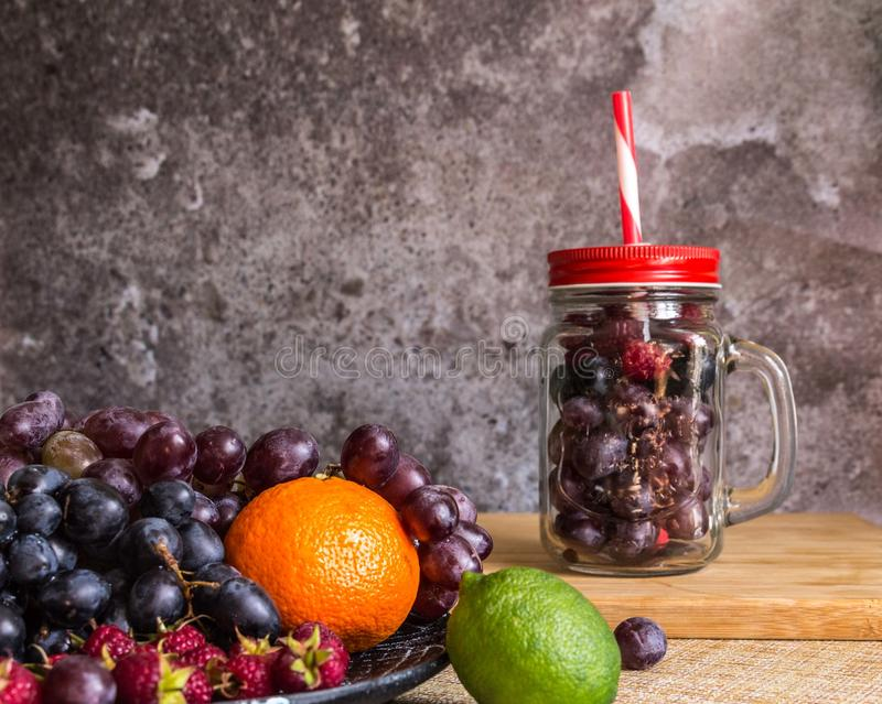 Smoothie jar shape fruits. Grapes, raspberry, lime, dark background royalty free stock photo