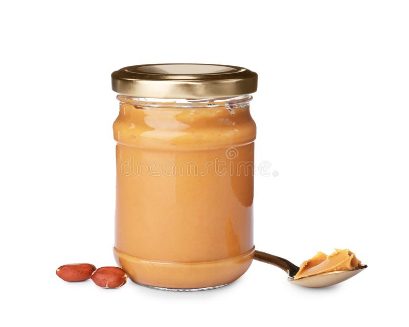 Jar and spoon with creamy peanut butter royalty free stock image