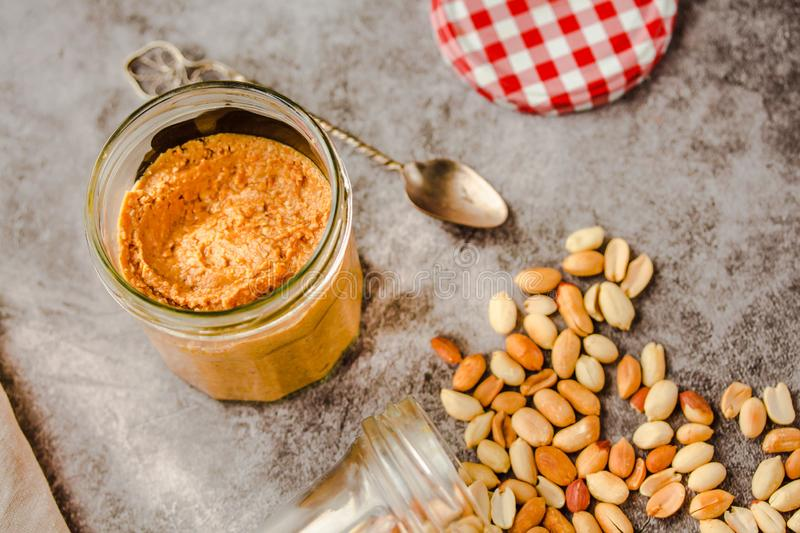 Jar and spoon of peanut butter and peanuts on dark wooden background from top view. Close-up royalty free stock photography