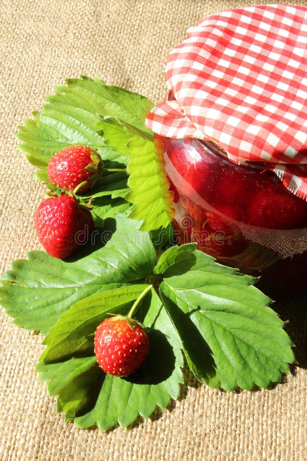 Jar of of strawberry jam with strawberries and leaves stock photos