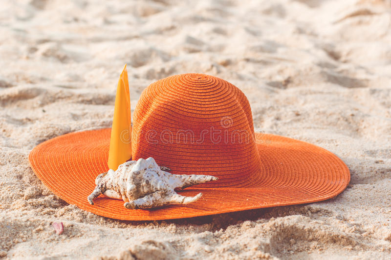 Jar of sunscreen lotion on the sandy beach. Sunscreen lotion in yellow jar with orange hat and shell on the beach with white sand royalty free stock photo