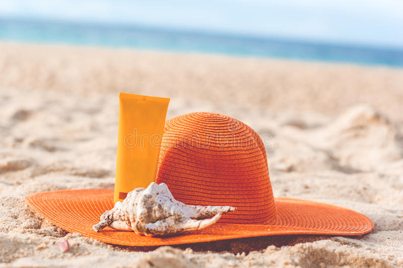 Jar of sunscreen lotion on the sandy beach. Sunscreen lotion in yellow jar with orange hat and shell on the beach with white sand, skincare concept stock photo