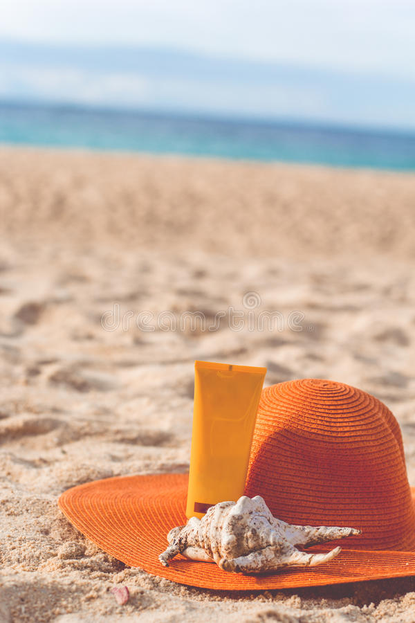 Jar of sunscreen lotion on the sandy beach. Sunscreen lotion in yellow jar with orange hat and shell on the beach with white sand, skincare concept, summertime stock photography