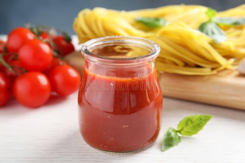 Jar of tasty tomato sauce on table stock photo