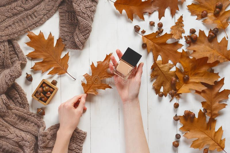 Jar with a tonal cream and oak autumn leaf in the woman`s hands. Top view. Natural beauty cosmetics concept. Autumn royalty free stock photography