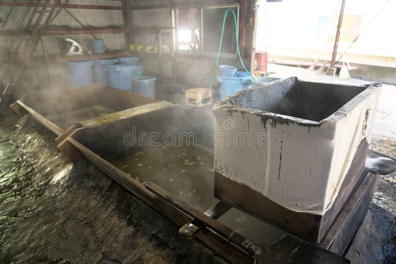 Jarabe de ebullición de la caña de azúcar en una cacerola para hacer el azúcar marrón en Amami Oshima, Kagoshima, Japón foto de archivo libre de regalías