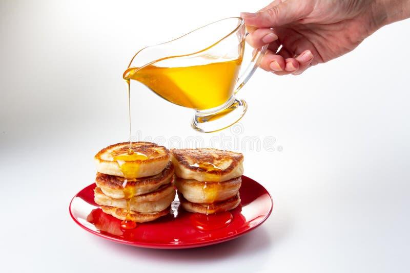 Jarabe de la miel en la crepe, comida deliciosa del postre en blanco, hecho en casa foto de archivo