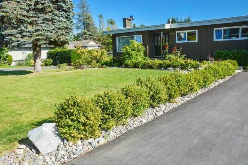 Jardín adornado con los arbustos verdes y la calzada del asfalto que lleva a la casa fotografía de archivo libre de regalías