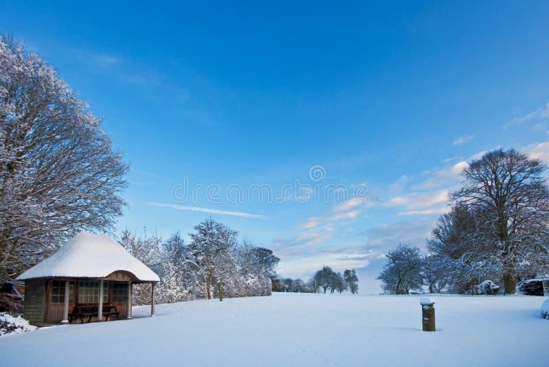 Jardín con el summerhouse cubierto en nieve fresca foto de archivo