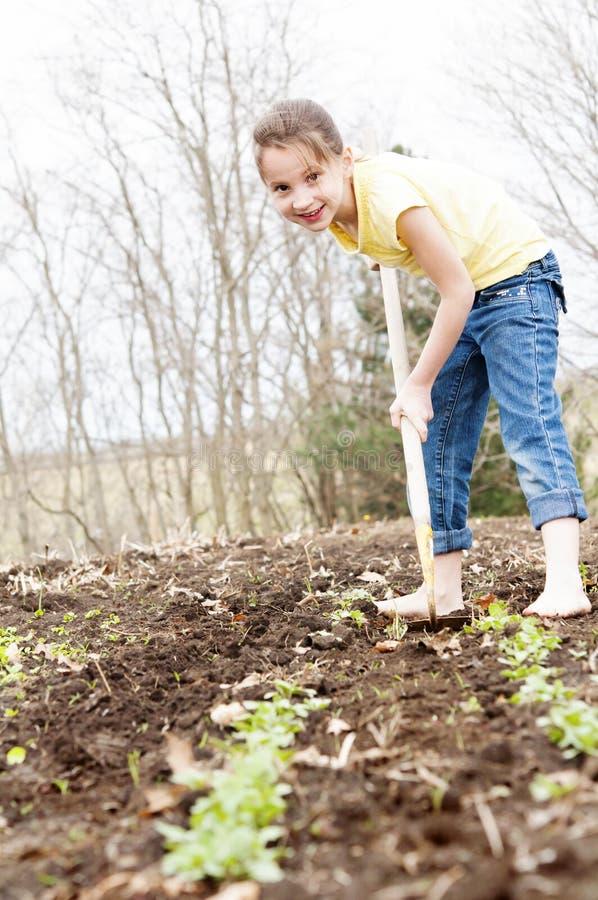 Jardín de azada de la primavera de la muchacha foto de archivo
