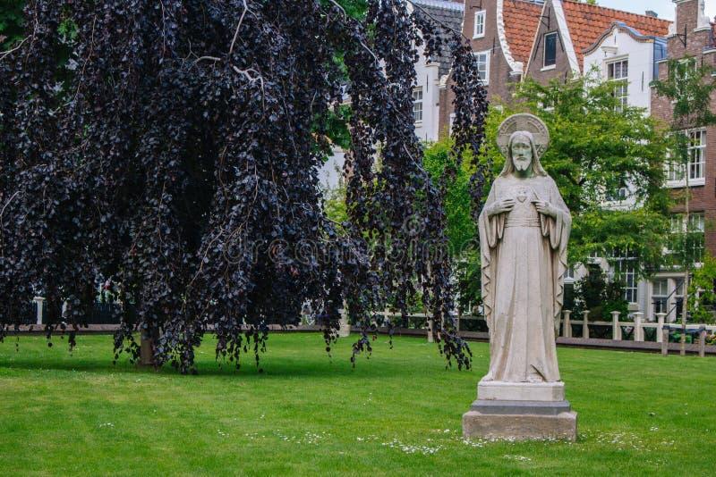 Jardín de Begijnhof con la estatua antigua de Jesus Christ Yarda medieval famosa con la escultura de Jesus Christ en Amsterdam fotografía de archivo
