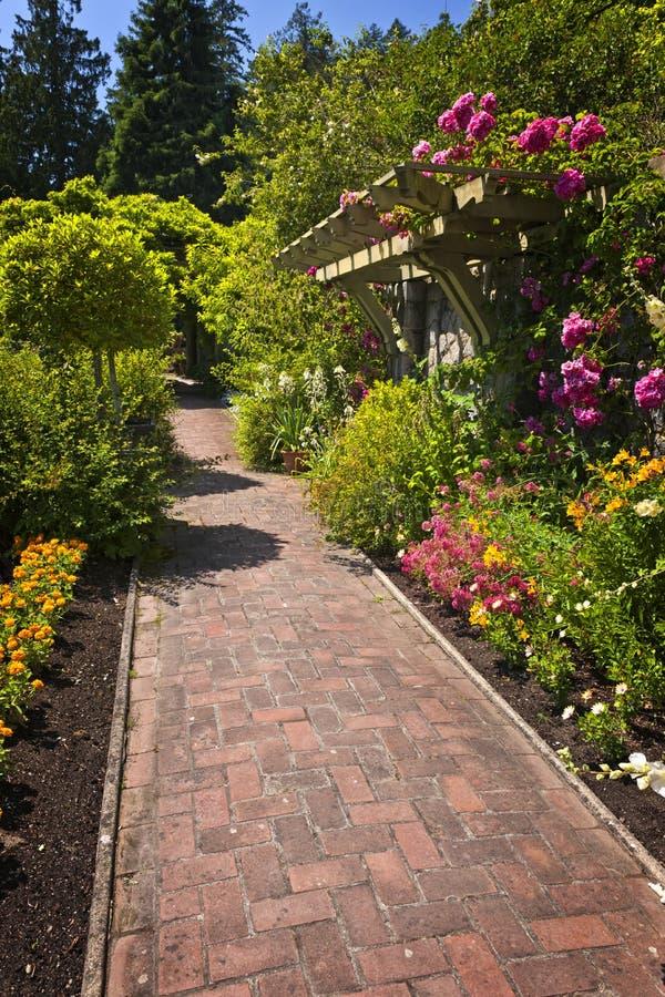 Jardín de flor con el camino pavimentado imagen de archivo libre de regalías