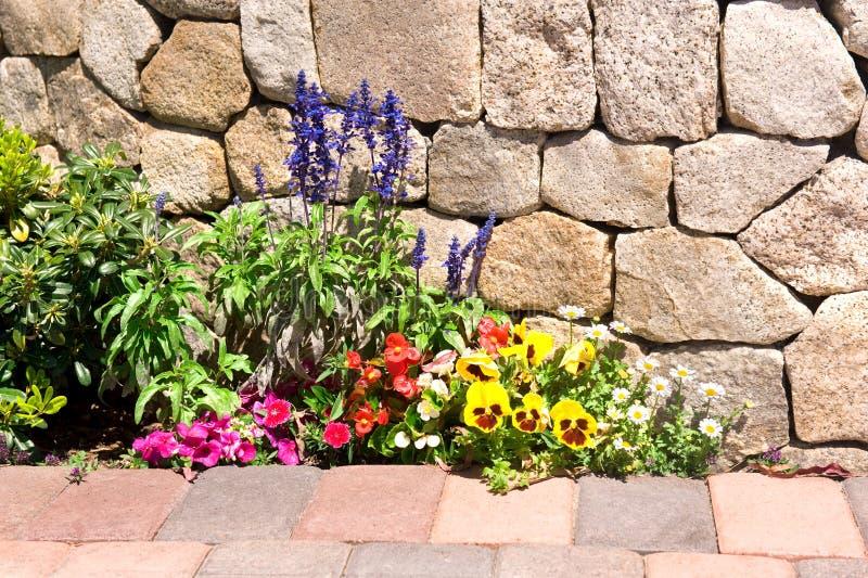 Jardín de flor a lo largo de la pared de piedra imágenes de archivo libres de regalías
