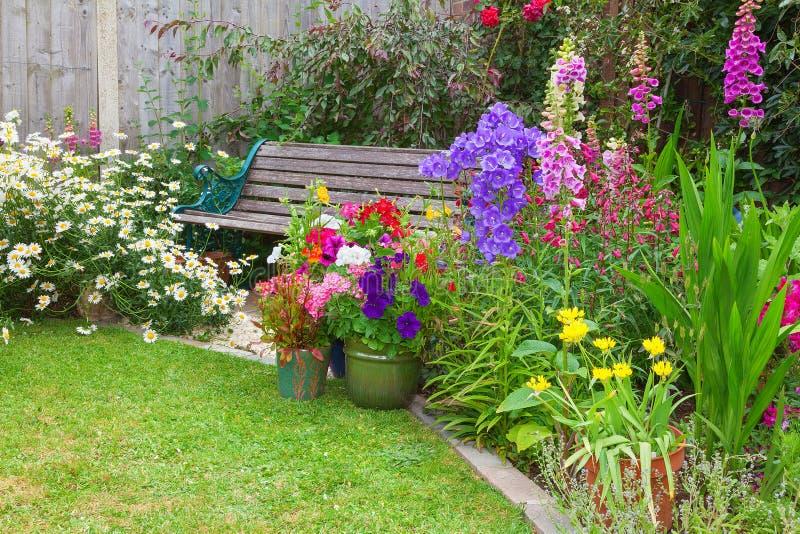 Jardín de la cabaña con el banco y envases por completo de flores foto de archivo libre de regalías