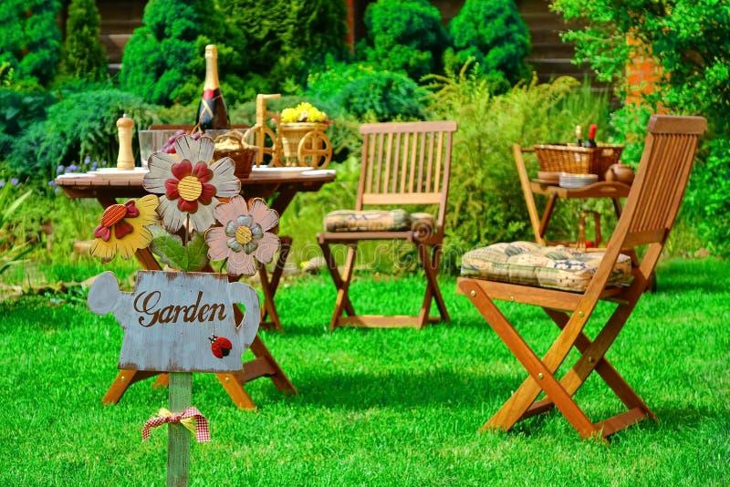 Jardín de la muestra en la placa de madera y los muebles al aire libre de madera fotos de archivo libres de regalías