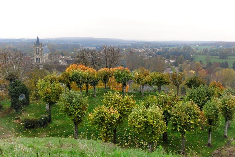 Jardín del árbol e iglesia vieja en un pueblo en Francia fotos de archivo libres de regalías