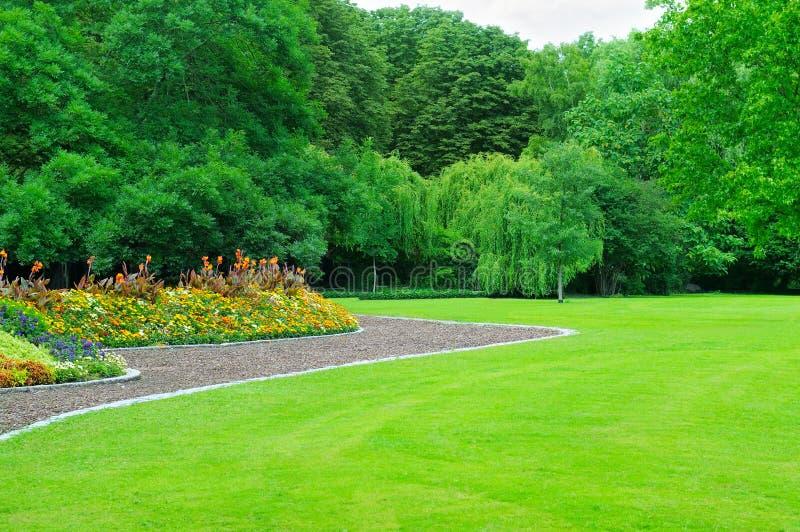 jardín con el césped y el jardín de flores imágenes de archivo libres de regalías