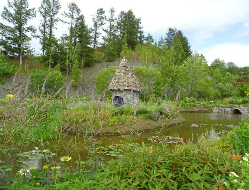 Jardín del verano con una casa linda del cuento de hadas en la charca imagen de archivo