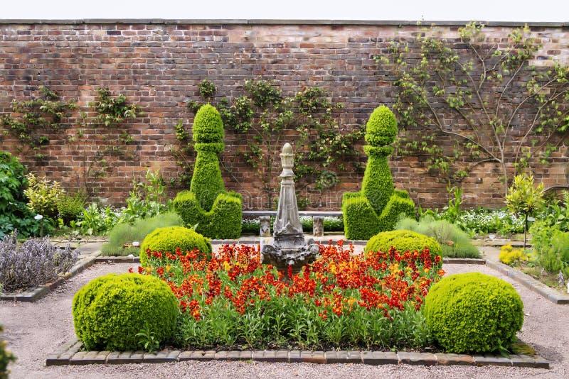 Jardín emparedado con el topiary y las flores rojas imágenes de archivo libres de regalías