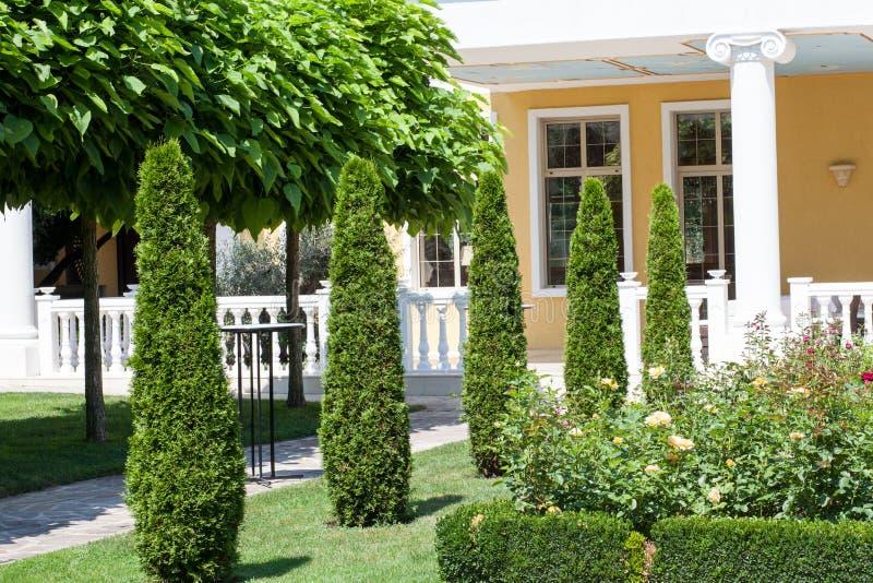 Jardín hermoso delante de una casa del chalet fotografía de archivo