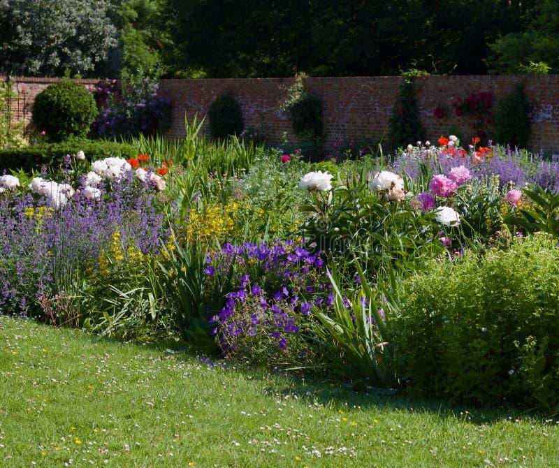 Jardín inglés de la cabaña con el césped en primero plano, cama de flor enorme y pared en fondo con el espacio de la copia - imag imagenes de archivo