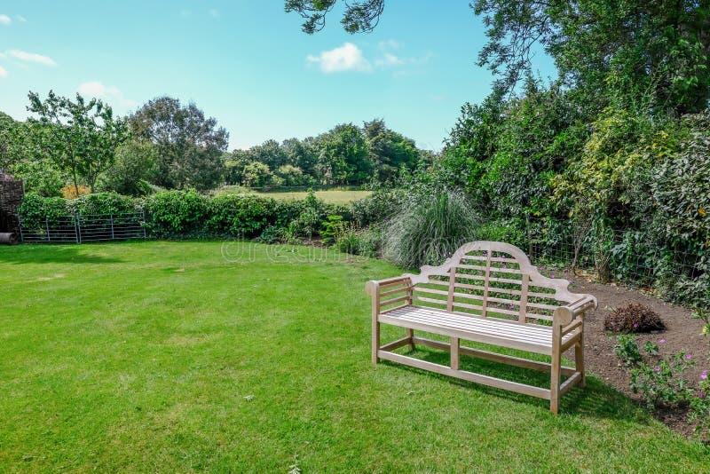 Jardín inglés tranquilo del país con la visión rural y el banco de madera fotos de archivo