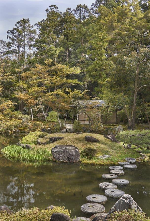Jardín japonés, una cabaña ocultada entre árboles de arce japonés y pinos fotografía de archivo
