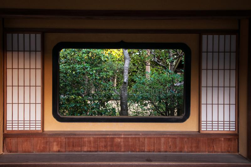 Jardín japonés visible a través de la ventana del estilo japonés imagen de archivo libre de regalías