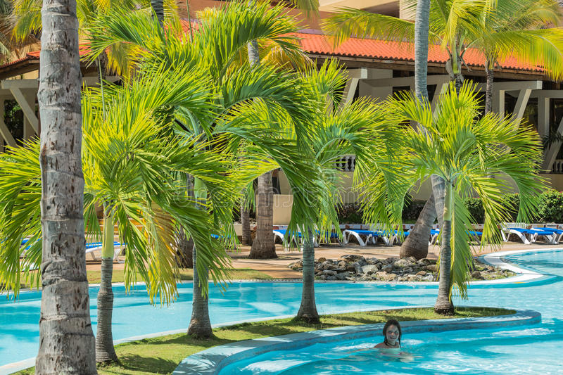 Jardín mullido natural de la palmera con la natación de la niña en la piscina fotografía de archivo libre de regalías