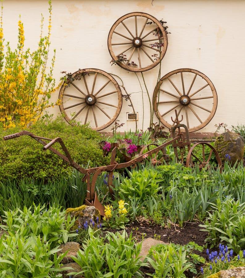 Jardín rural adornado con las ruedas del carro fotos de archivo libres de regalías