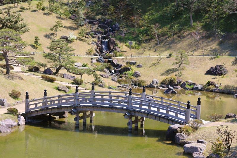 Jardín tradicional japonés con la charca del puente de madera imagen de archivo libre de regalías